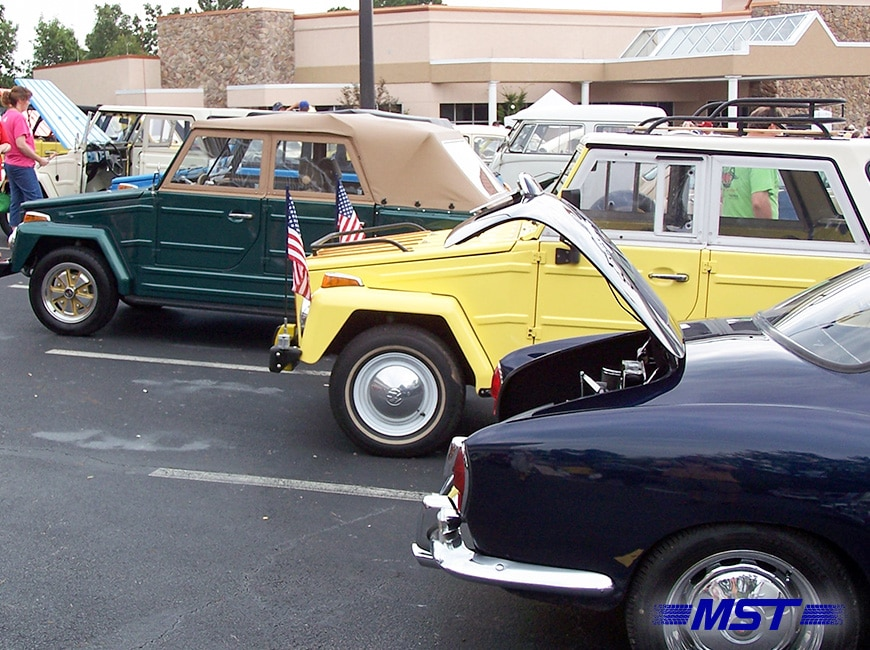 classic cars in a line in a parking lot